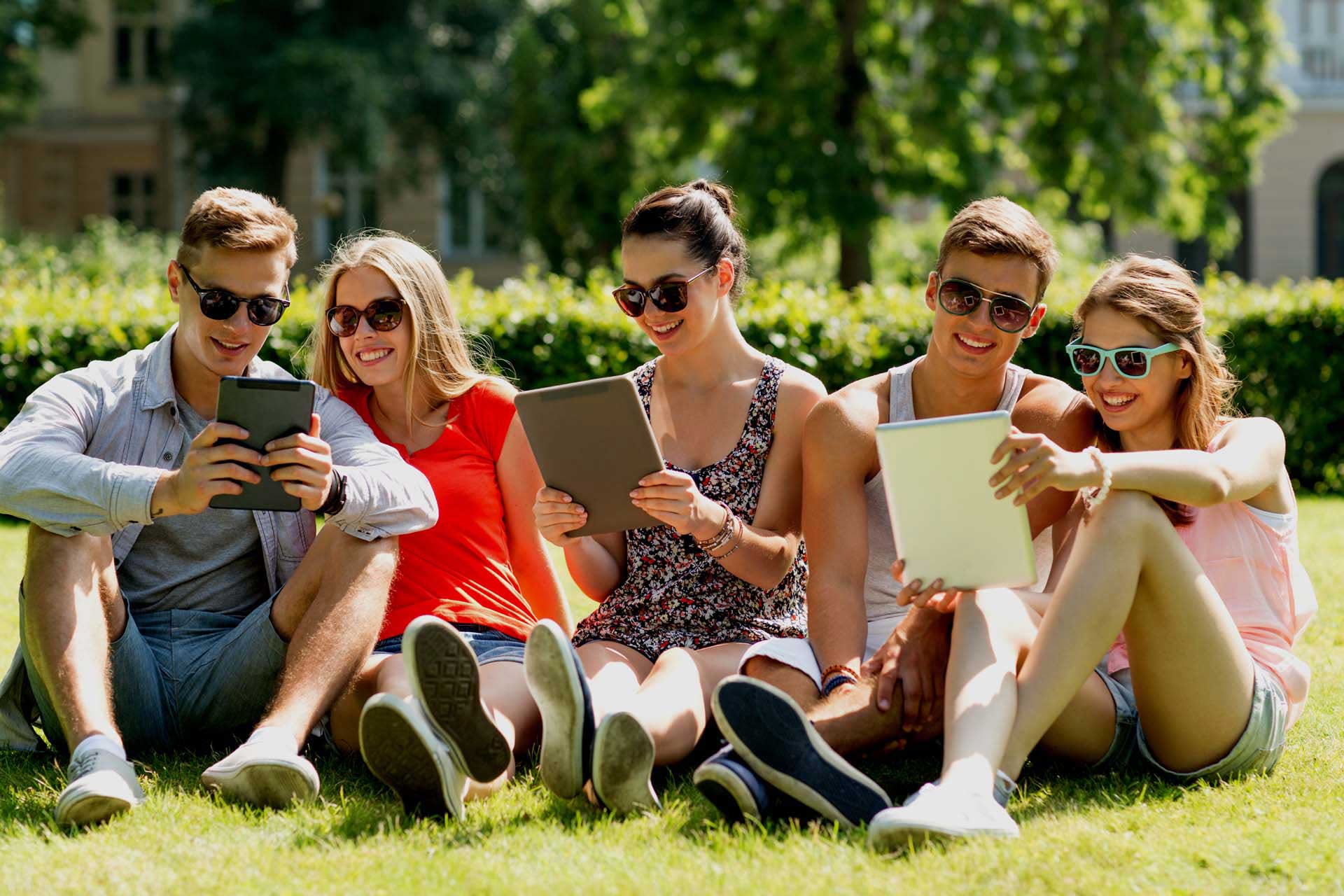 group of people on the grass looking at their mobile devices